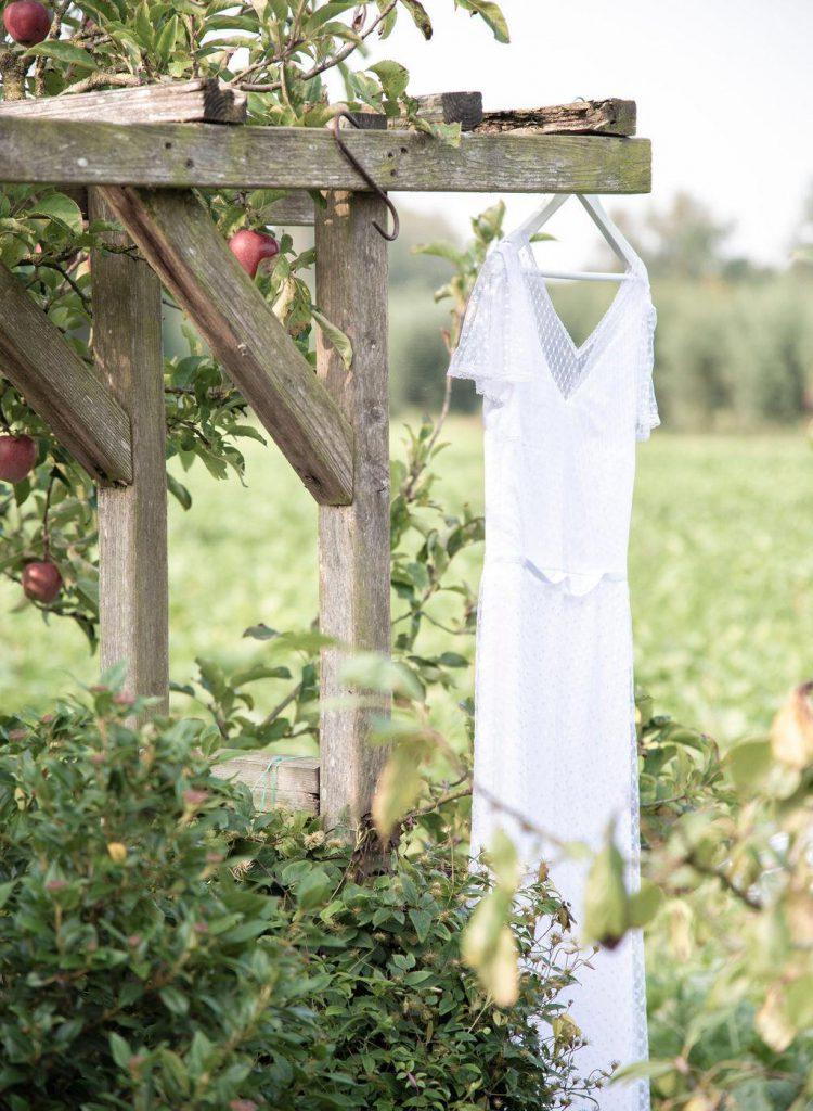 Bruidsjurk aan hangertje in de tuin